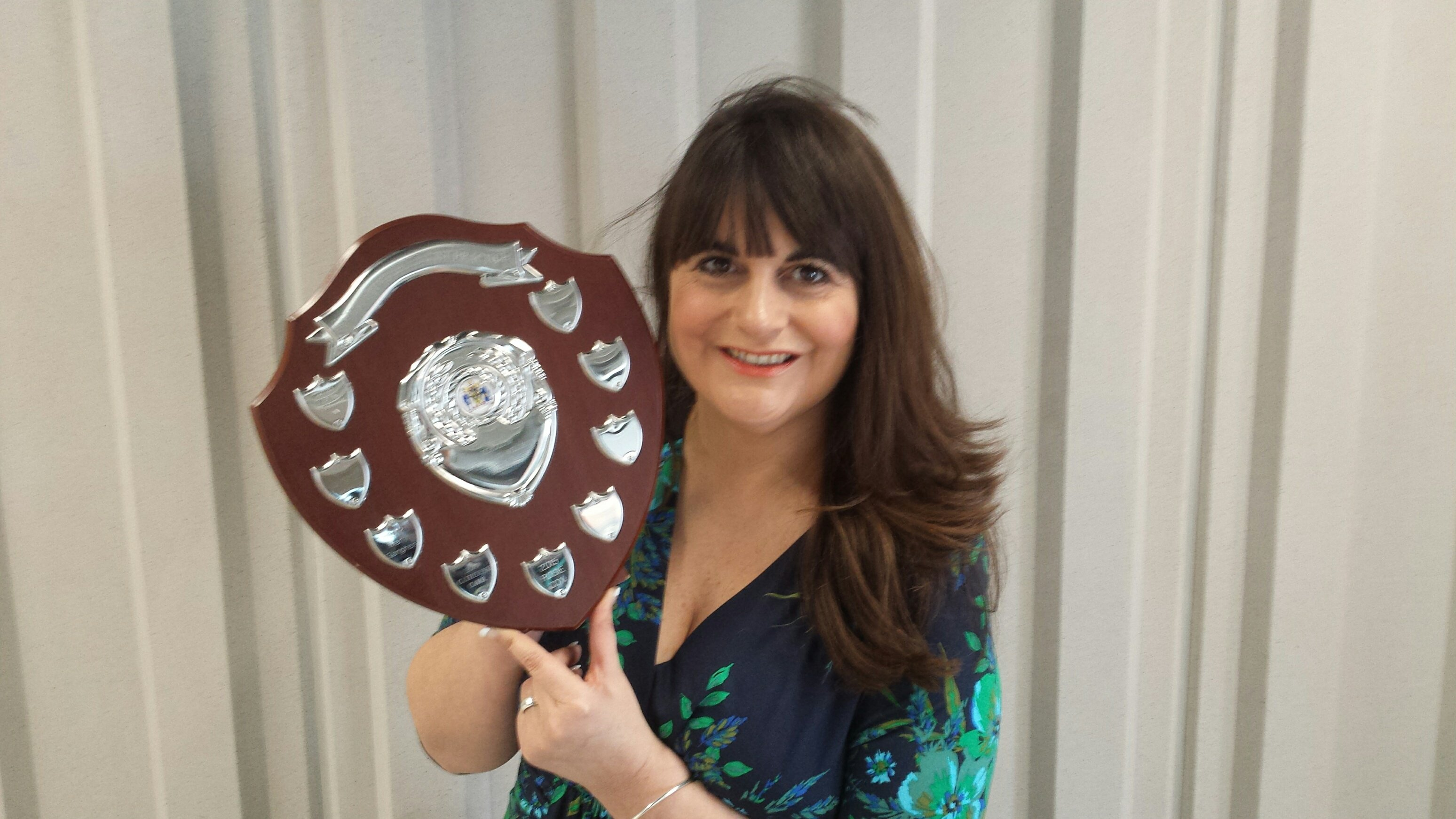 School nurse holding award