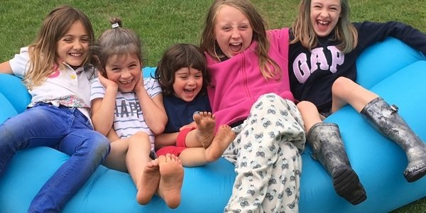 Children sitting on a blow up sofa