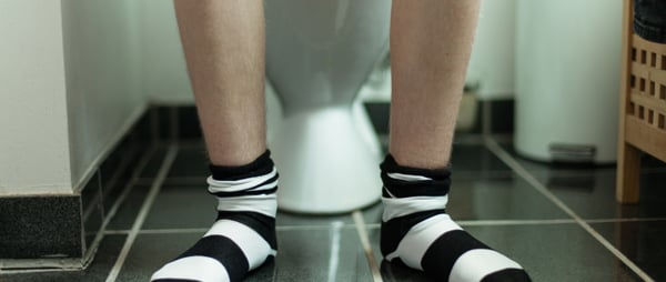 Boy with stripy socks on toilet
