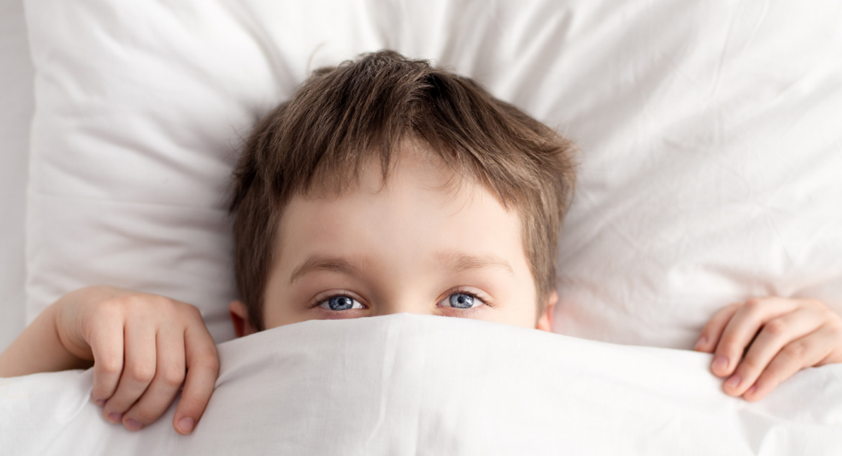 Boy in bed with covers up