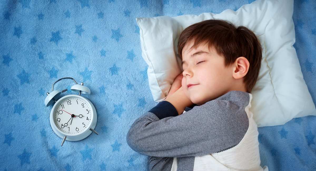 Boy in bed next to an alarm clock