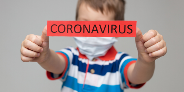 Child holding a sign saying Coronavirus