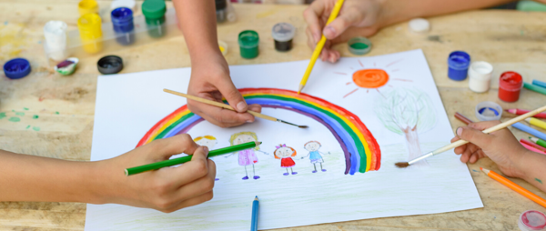 Hands drawing a rainbow